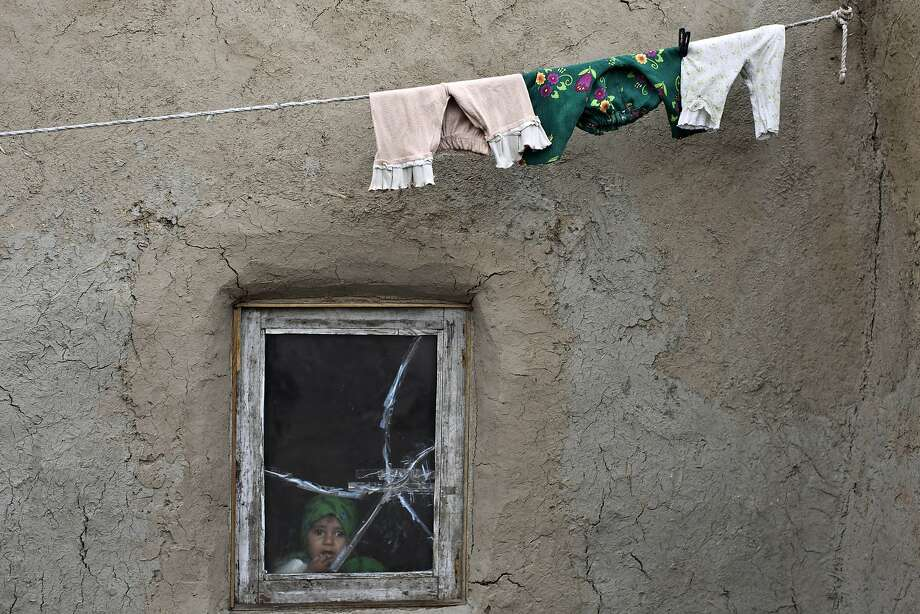 An Afghan girl looks out the window of her home in Kabul, Afghanistan, Thursday, April 3, 2014. (AP Photo/Muhammed Muheisen) Photo: Muhammed Muheisen, Associated Press