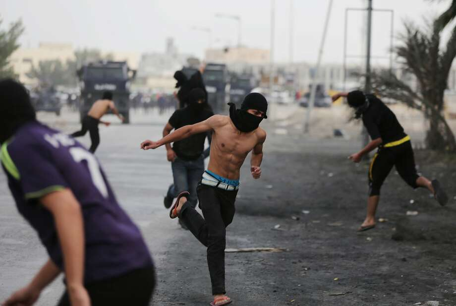 Bahraini anti-government protesters carrying stones challenge riot police firing tear gas and shotguns during clashes in Eker, Bahrain, on Thursday, April 3, 2014. Clashes erupted after the funeral for Hussain Ahmed Sharaf, 21, a wanted protester whose family maintains was killed by police. During the funeral procession, mourners shouted anti-government slogans and chanted against the Formula One Bahrain Grand Prix being held Sunday in the Gulf island kingdom. (AP Photo/Hasan Jamali) Photo: Hasan Jamali, Associated Press