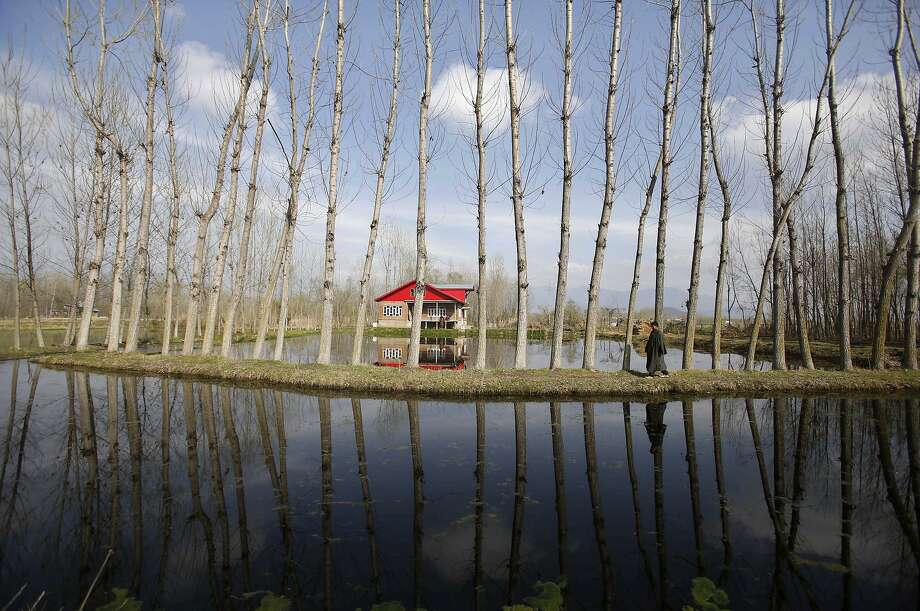 A Kashmiri man is reflected in a canal as he walks on the outskirts of Srinagar, India, Thursday, April 3, 2014. (AP Photo/Mukhtar Khan) Photo: Mukhtar Khan, Associated Press