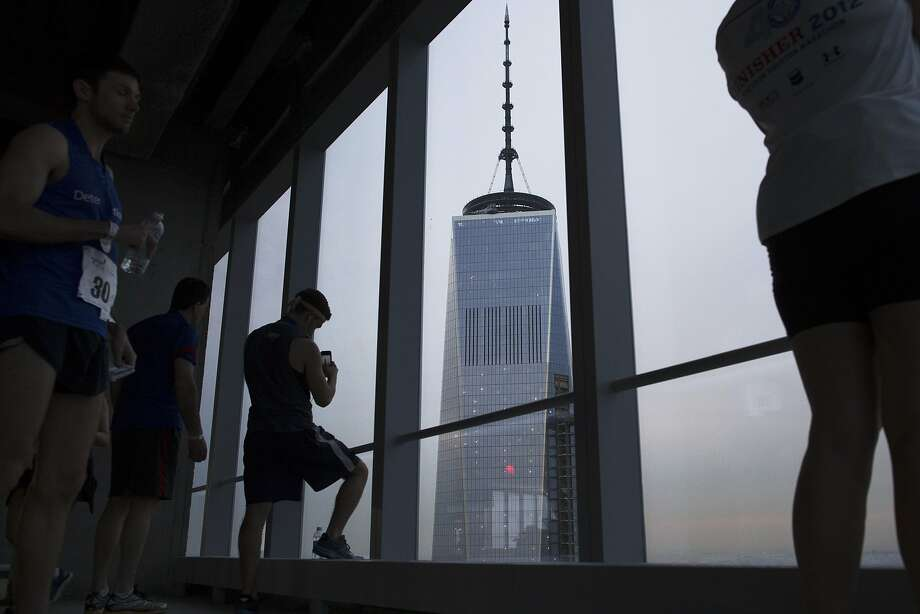"Runners enjoy the view of the 1 World Trade Center from the 72nd floor of 4 World Trade Center during the ""Runyon Up,"" a fundraiser for the Damon Runyon Cancer Research Foundation, Thursday, April 3, 2014, in New York. More than 700 people took part in the climb with the fastest male contender reaching the finish in just under 9 minutes and the first woman clocking in at just over 11 minutes. (AP Photo/John Minchillo) Photo: John Minchillo, Associated Press"