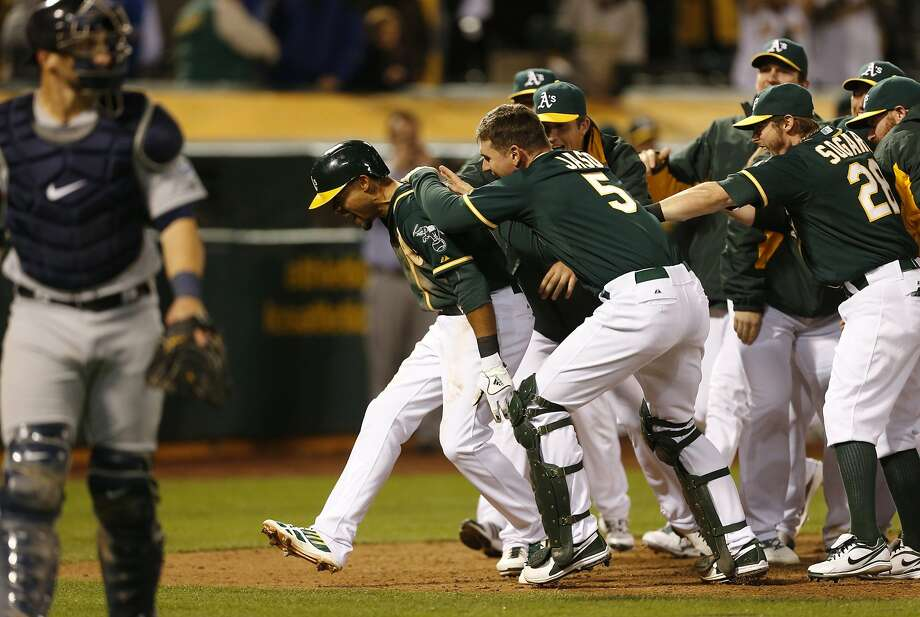 Coco Crisp is congratulated after his home run leading off the bottom of the 12th inning gave the A's a victory. Photo: Beck Diefenbach, Associated Press