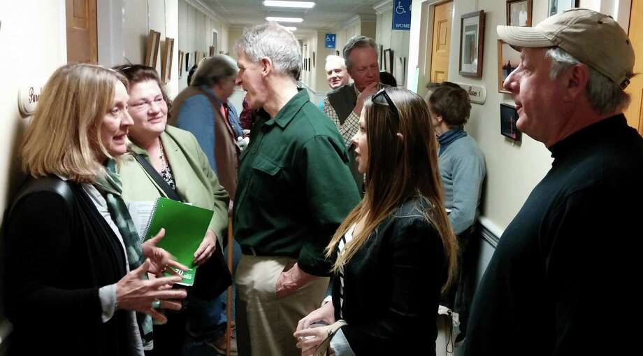 Opponents of a proposed 96-unit apartment building on lower Bronson Road talk in a hallway of Sullivan-Independence Hall after the town's Inland Wetlands Commission voted to approve the project. Photo: Andrew Brophy / Fairfield Citizen