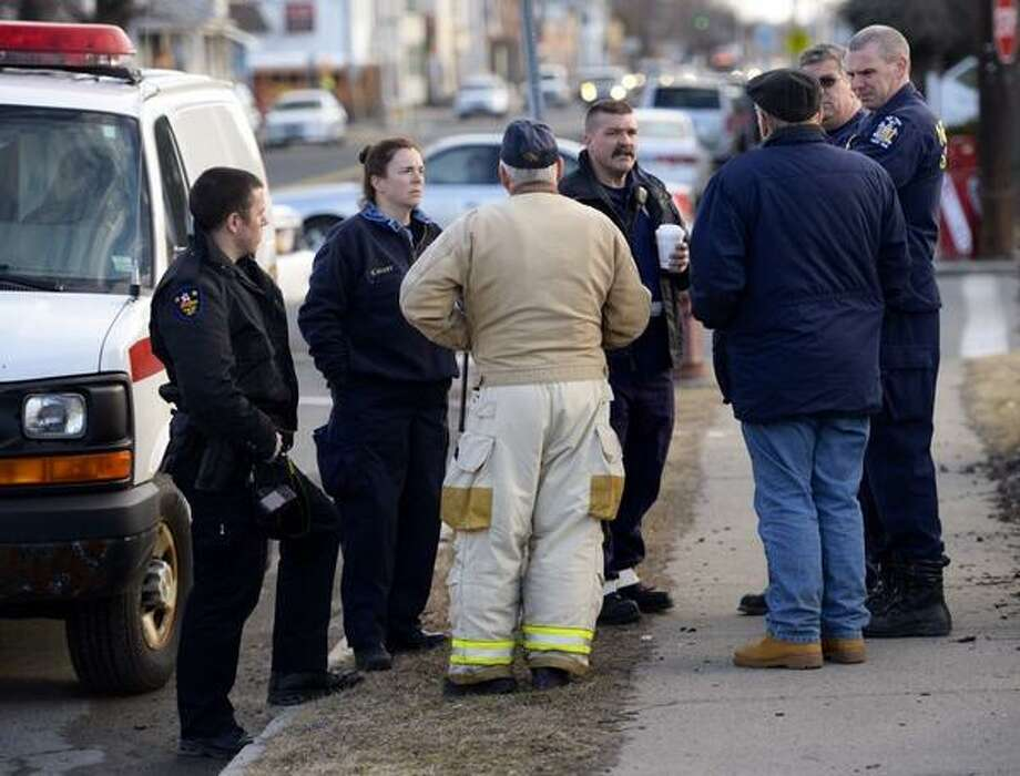 State fire investigators, Troy police and firefighters huddle at the scene of a fatal fire at 269 and 271 Fifth Ave., in Troy on Friday, April 4, 2014. (Skip Dickstein / Times Union)