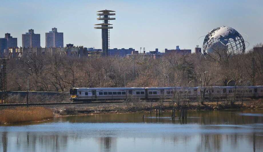 "A space-age tower, left, and a giant metal globe called the Unisphere, right, structures remaining from the 1964 World's Fair, looms above a passing LIRR train on Tuesday April 1, 2014 in the Queens borough of New York.  As this month's 50th anniversary of the 1964 New York World's Fair approaches, a debate has emerged about what to do with some of the fair's most famous structures. The towers topped by flying-saucer-like platforms, and a pavilion of pillars once called the ""Tent of Tomorrow,"" still sit as abandoned relics in the middle of Queens' Flushing Meadows Corona Park.   (AP Photo/Bebeto Matthews) ORG XMIT: NYBM301 Photo: Bebeto Matthews, AP / AP"