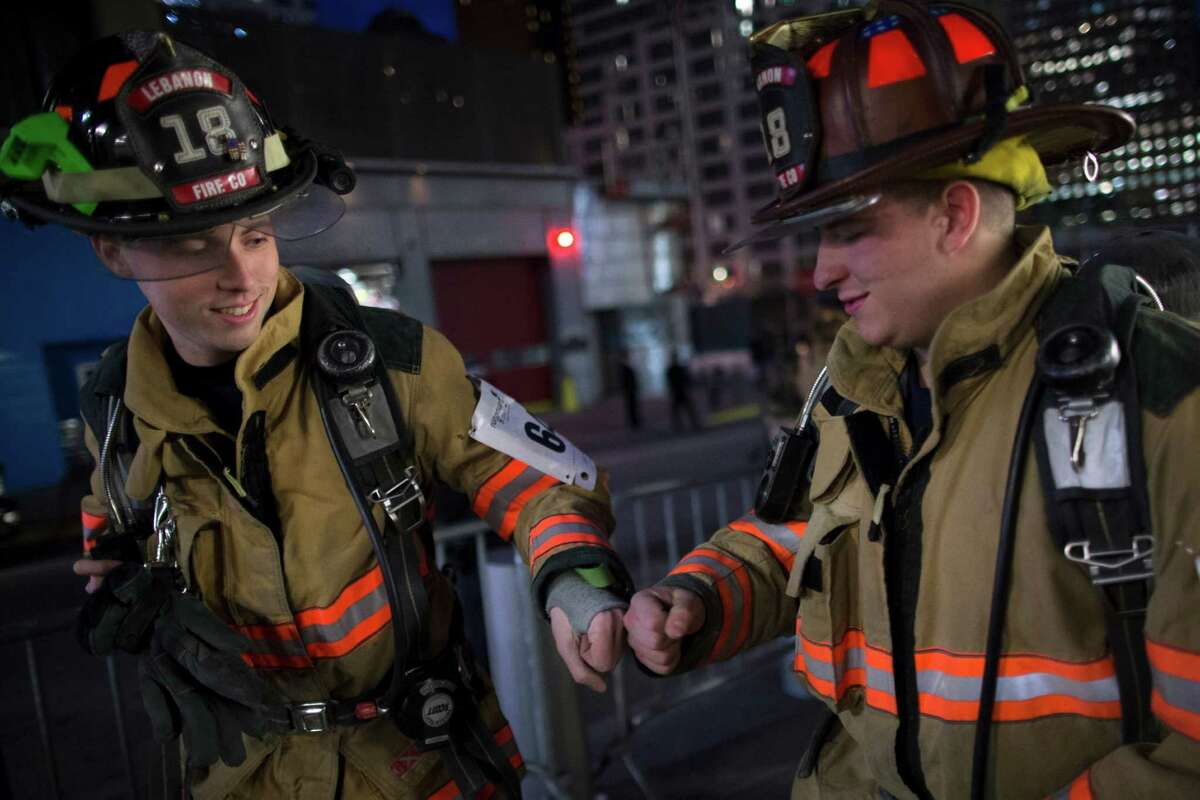 Firefighters from departments outside New York support each other before a climb towards the 72nd floor of 4 World Trade Center during the