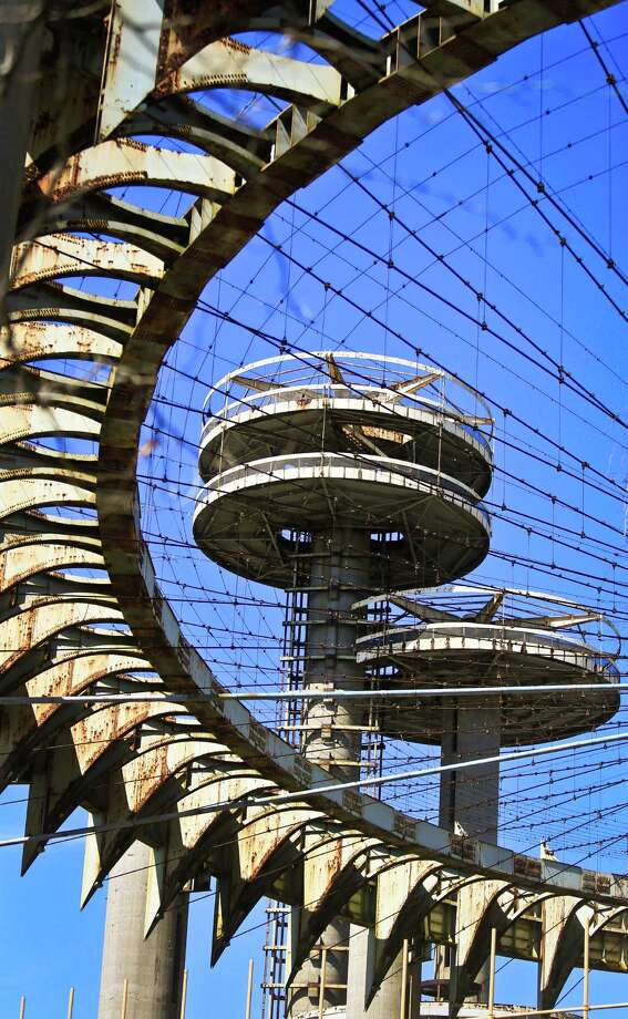 "Space-age towers, topped by flying-saucer-like platforms, and a pavilion of pillars once called the ""Tent of Tomorrow,"" looms as relics remaining from the 1964 World's Fair, on Tuesday April 1, 2014 in the Queens borough of New York.  As this month's 50th anniversary of the 1964 New York World's Fair approaches, a group of preservationists is fighting to save the pavilion, but others see them as annoying eyesores that should be torn down. Neither option would come cheap: an estimated $14 million for demolition and up to $72 million for renovation.  (AP Photo/Bebeto Matthews) ORG XMIT: NYBM304 Photo: Bebeto Matthews, AP / AP"