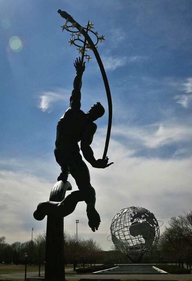 A restored statue and a giant metal globe called the Unisphere, are remaining symbols from the 1964 World's Fair, Tuesday April 1, 2014 in the Queens borough of New York.  As this month's 50th anniversary of the 1964 New York World's Fair approaches, a group of preservationists is fighting to other structures some see as annoying eyesores that should be torn down.  (AP Photo/Bebeto Matthews) ORG XMIT: NYBM307 Photo: Bebeto Matthews, AP / AP