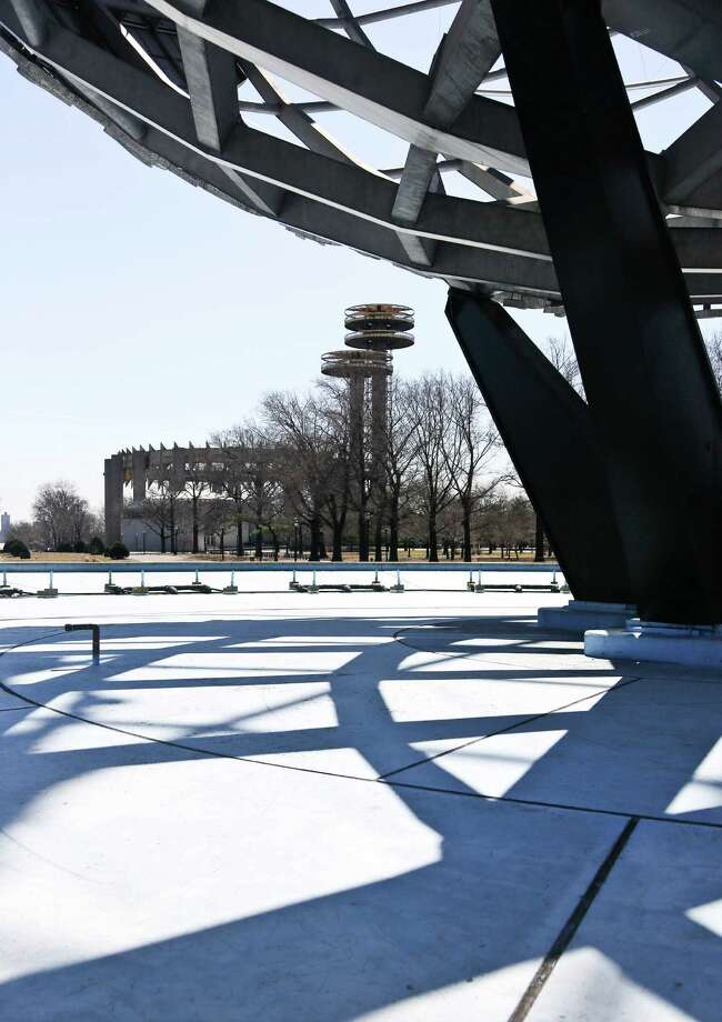 "A space-age tower, left, is viewed near a giant metal globe called the Unisphere, structures remaining from the 1964 World's Fair, on Tuesday April 1, 2014 in the Queens borough of New York.  As this month's 50th anniversary of the 1964 New York World's Fair approaches, a debate has emerged about what to do with some of the fair's most famous structures. The towers topped by flying-saucer-like platforms, and a pavilion of pillars once called the ""Tent of Tomorrow,"" still sit as abandoned relics in the middle of Queens' Flushing Meadows Corona Park.   (AP Photo/Bebeto Matthews) ORG XMIT: NYBM310 Photo: Bebeto Matthews, AP / AP"