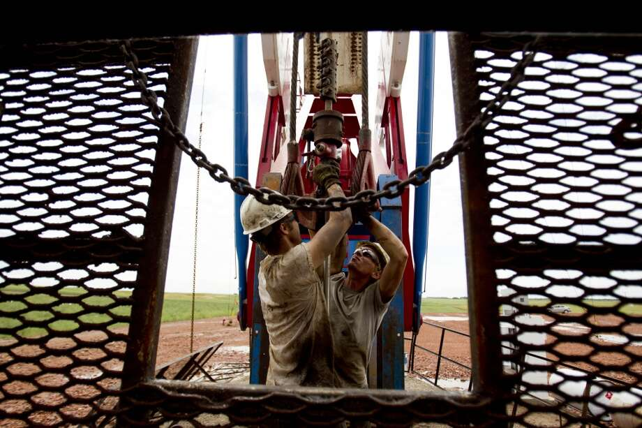 Austin Mitchell (left) and Ryan Lehto work on an oil derrick outside of Williston, N.D. in 2011. Photo: Gregory Bull, Associated Press