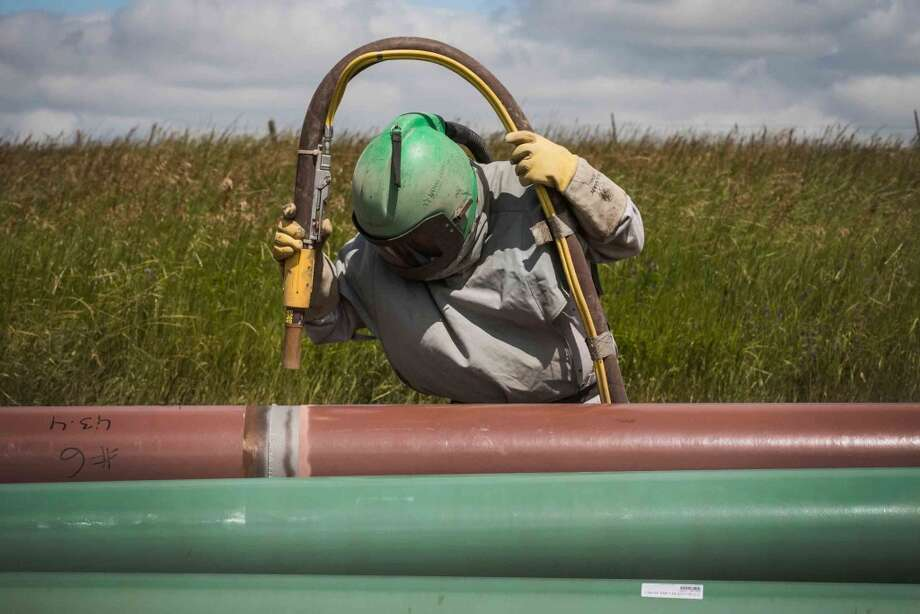 A construction worker specializing in pipe-laying sandblasts a section of pipeline in July 2013 outside Watford City, North Dakota. North Dakota is currently experiencing an oil boom, creating thousands of jobs throughout the state and billions of dollars in new state revenue. Local two-lane roads that are used to access drill sites have taken a beating due to the unprecedented amount of traffic. Pipelines are being constructed across the state in part to streamline the movement of oil from drill sites to train depots and oil refineries. Photo: Andrew Burton, Getty Images