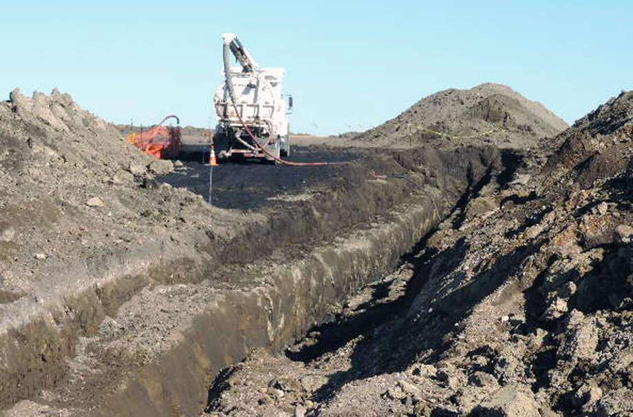 Vacuum trucks cleans up oil in near Tioga, N.D. in October 2013. The North Dakota Health Department says more than 20,000 barrels of crude oil have spewed out of a Tesoro Corp. oil pipeline in a wheat field in northwestern North Dakota. Photo: Uncredited, Associated Press
