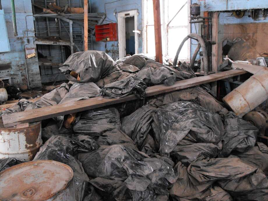 Bags full of radioactive oil filter socks, the nets that strain liquids during the oil production process, are piled in an abandoned building in Noonan, N.D. in March 2014. North Dakota will pay for the cleanup of the illegally dumped radioactive waste, according to  documents. Photo: Associated Press
