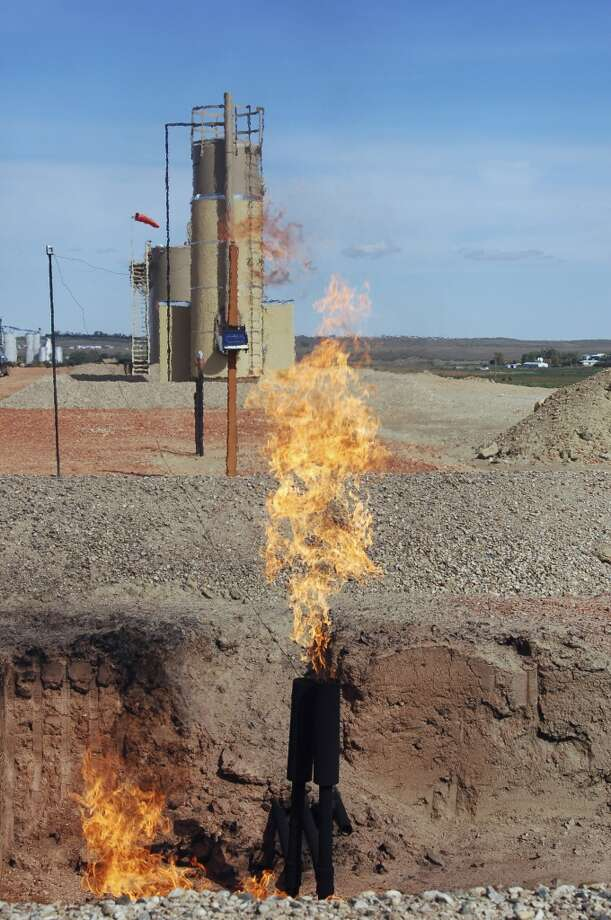 Natural gas is flared from an oil well near Parshall, N.D. in 2008. North Dakota regulators are holding public hearings in 2014 on  plans to reduce the flaring of natural gas in the western oil fields. North Dakota drillers currently burn off, or flare, more than 30 percent of the valuable gas, compared to the national average of less than 1 percent. Photo: James MacPherson, Associated Press