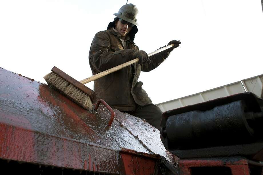 Ray Gerish, a Raven Drilling worker, cleans equipment on a drilling rig near Watford City, N.D. in 2013. Photo: Jerry Burnes, Associated Press