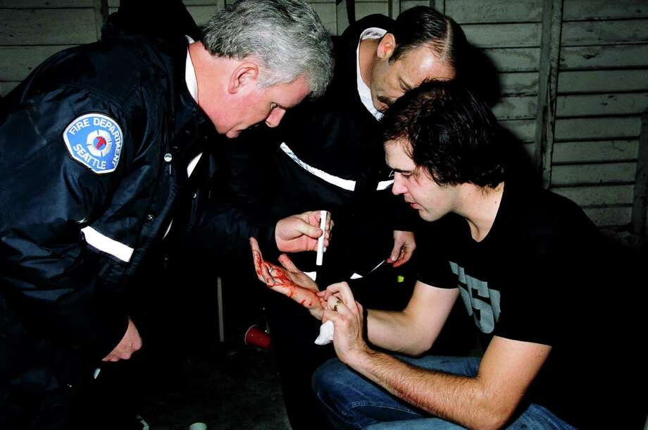 Krist Novoselic of Nirvana and firefighters backstage at the MTV Live and Loud-Nirvana Performs in December 1993 at Pier 28 in Seattle. Photo: Jeff Kravitz, Getty / FilmMagic, Inc