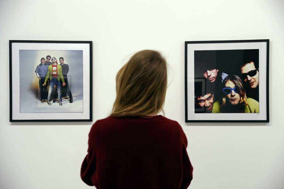 "A woman looks at photos of late singer Kurt Cobain posing with members of his band Nirvana, as part of the exhibition ""The Last Shooting"" on March 28, 2014 at the Addict gallery in Paris. French photographer Youri  Lenquette exhibits a series of photos he took of Nirvana frontman during a February 1994 session, weeks before Cobain committed suicide at the age of 27, near the height of his grunge-rock band's success. The exhibition runs through March 25 - June 21, 2014. Photo: BERTRAND GUAY, Getty / 2014 AFP"