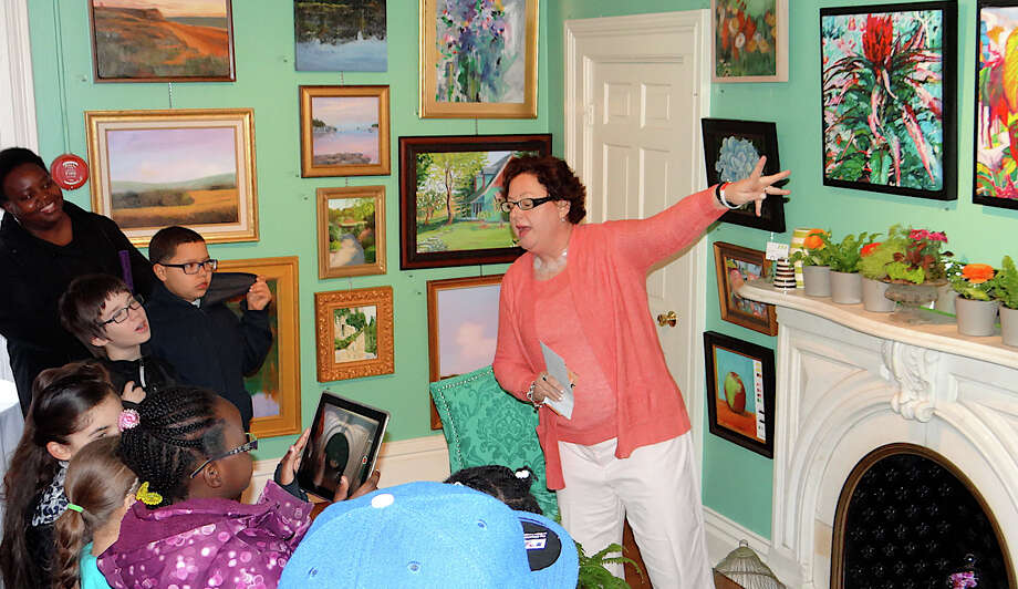 Patricia Boyd discusses artwork with Thomas Hook School students at the Friday opening of the Junior League of Eastern Fairfield County's 22nd annual Art Show in the Burr Homestead. Photo: Mike Lauterborn / Fairfield Citizen