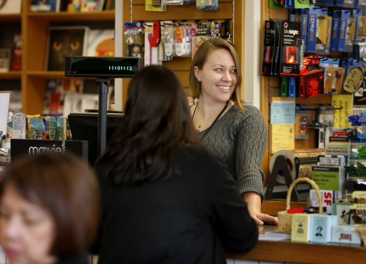 Briah Skelly, a clerk and supervisor at Books Inc in the Opera plaza, makes a modest amount over minimum wage, and loves working in the bookstore Thursday April 3, 2014 in San Francisco, Calif. Michael Tucker, the president of Books Inc., says increasing the minimum wage to $15 and the cost of healthcare will force him to close stores and lay off workers at his ten locations.