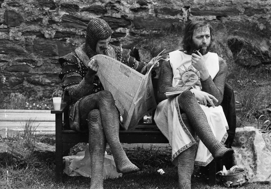 1974:  A chainmail-clad John Cleese reads a newspaper while Graham Chapman smokes a quiet pipe on the set of 'Monty Python and the Holy Grail'. Photo: John Downing, Getty Images
