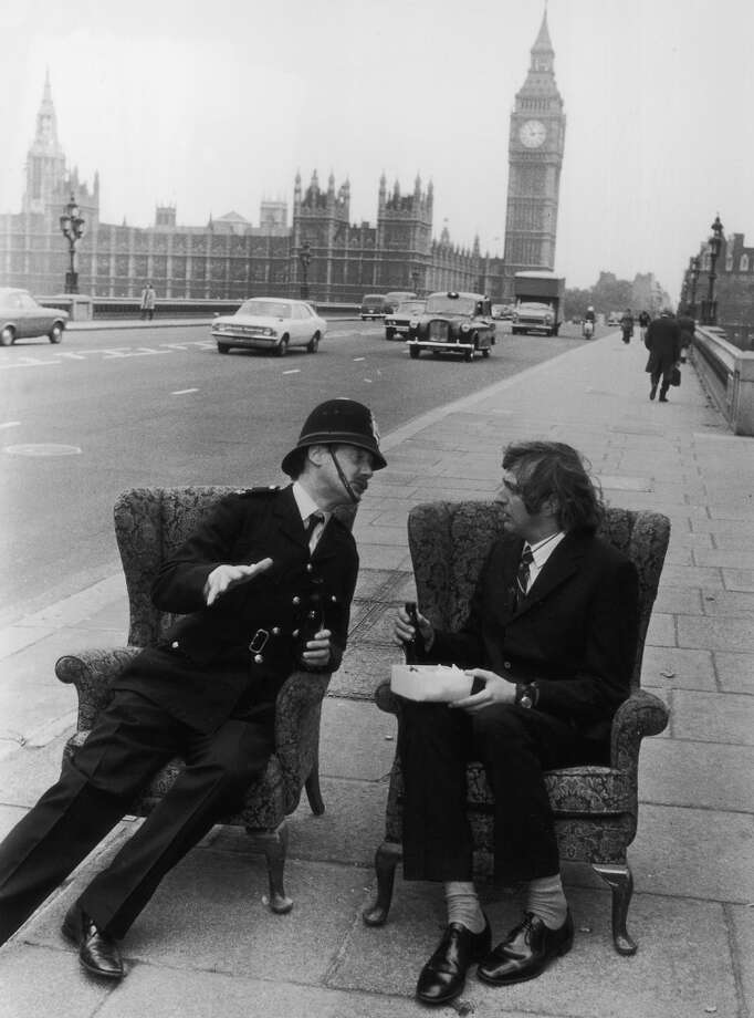 1974: British actors, writers and comedians Graham Chapman (1941 - 1989 ) and Michael Palin (in police uniform) sitting in armchairs on Westminster Bridge, London. Photo: Evening Standard, Getty Images