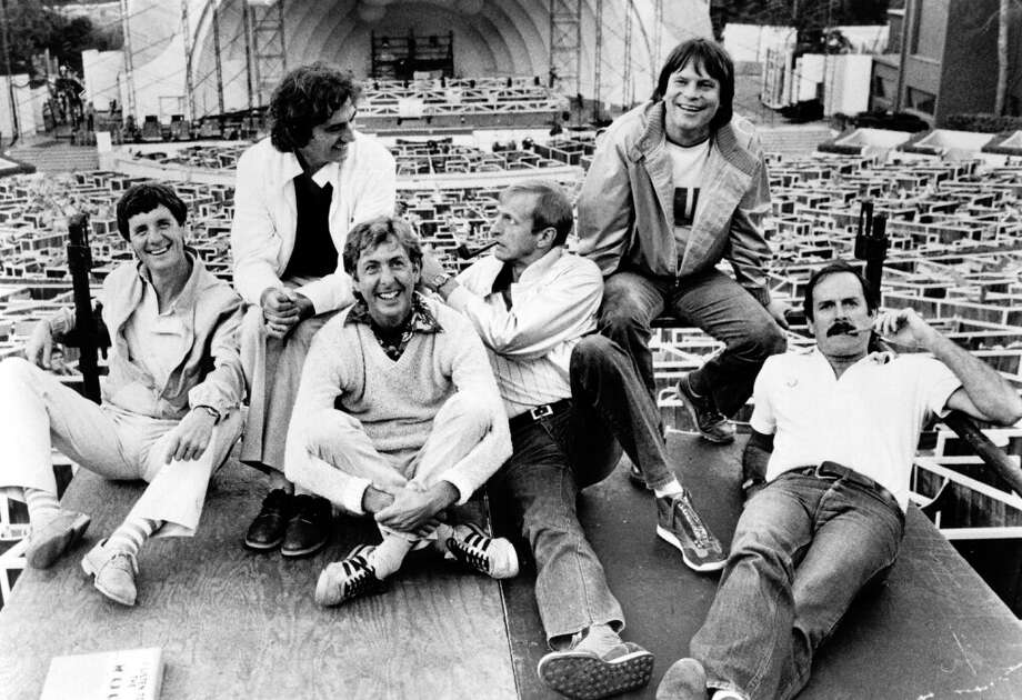 1982: British comedy troupe Monty Python including (left to right) Michael Palin, Terry Jones, Eric Idle, Graham Chapman (1941 - 1989), Terry Gilliam, and John Cleese, lounge about at the site of their filmed live show at the Hollywood Bowl, Hollywood. Photo: Hulton Archive, Getty Images