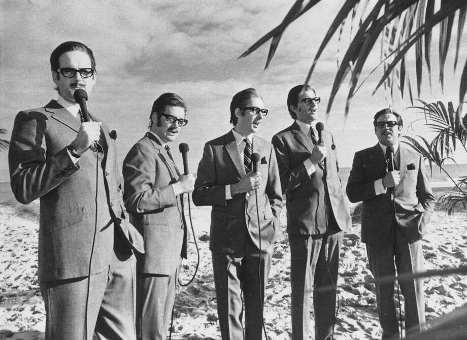 1971: The Monty Python team imitate journalist and broadcaster Alan Whicker. Left to right: John Cleese, Michael Palin, Eric Idle, Graham Chapman (1941 - 1989) and Terry Jones. Photo: Alan Howard, Getty Images