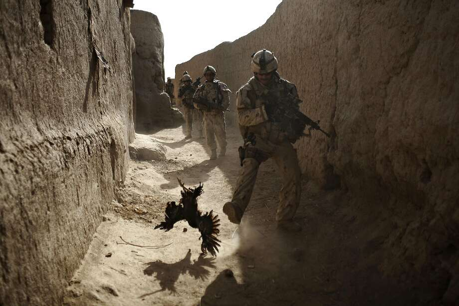 FILE - In this Saturday, Sept. 11, 2010 file photo made by Associated Press photographer Anja Niedringhaus, a Canadian soldier with the 1st RCR Battle Group, The Royal Canadian Regiment, chases a chicken seconds before he and his unit were attacked by grenades shot over the wall during a patrol in Salavat, southwest of Kandahar, Afghanistan. Niedringhaus, 48, an internationally acclaimed German photographer, was killed and an AP reporter was wounded on Friday, April 4, 2014 when an Afghan policeman opened fire while they were sitting in their car in eastern Afghanistan. (AP Photo/Anja Niedringhaus, File) Photo: Anja Niedringhaus, Associated Press