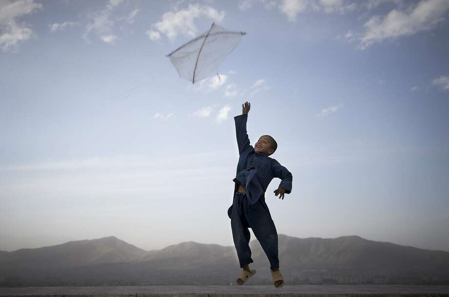 In this 2013 photo by Anja Niedringhaus, an Afghan boy flies his kite on a hill overlooking Kabul. Photo: Anja Niedringhaus, Associated Press