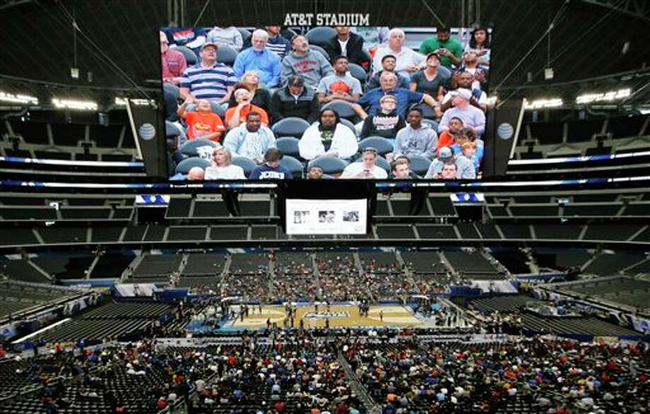 Fans watch Connecticut during  the team's practice for their NCAA Final Four tournament college  basketball semifinal game Friday, April 4, 2014, in Dallas. Connecticut  plays Florida on Saturday, April 5, 2014. (AP Photo/Tony Gutierrez)