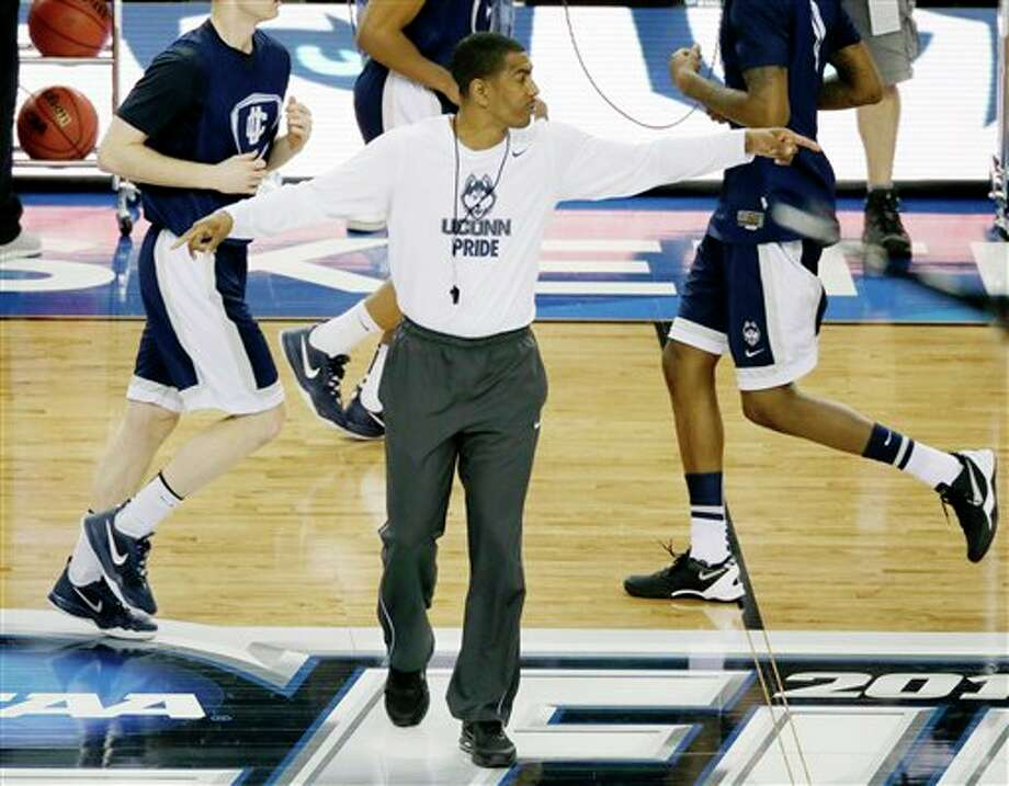 Connecticut head coach Kevin  Ollie runs practice for their NCAA Final Four tournament college  basketball semifinal game Friday, April 4, 2014, in Dallas. Connecticut  plays Florida on Saturday, April 5, 2014. (AP Photo/Tony Gutierrez)