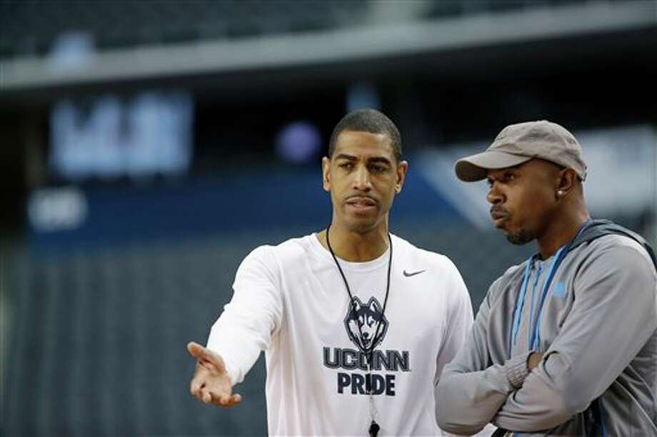 Connecticut head coach Kevin  Ollie and former professional basketball player Greg Anthony talk during  Connecticut's practice for their NCAA Final Four tournament college  basketball semifinal game Friday, April 4, 2014, in Dallas. Connecticut  plays Florida on Saturday, April 5, 2014. (AP Photo/David J. Phillip)
