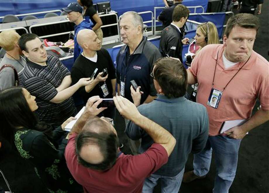 Former Connecticut head coach  Jim Calhoun, center rear, is interviewed by members of the media during  the team's practice for their NCAA Final Four tournament college  basketball semifinal game Friday, April 4, 2014, in Dallas. Connecticut  plays Florida on Saturday, April 5, 2014. (AP Photo/Charlie Neibergall)