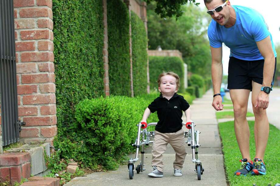 Stephen Cunningham walks with his son, Oliver, 2, outside their family home Wednesday, April 2, 2014, in Houston.  Cunningham, is competing in his second Ironman Saturday during the Memorial Hermann Ironman 70.3 TEXAS in Galveston. Cunningham, who's son has Spina Bifida, says he's doing this to show his son that you can do anything you put your mind to as long as you're willing to work hard for it.  ( Johnny Hanson / Houston Chronicle ) Photo: Johnny Hanson, Staff / © 2014  Houston Chronicle