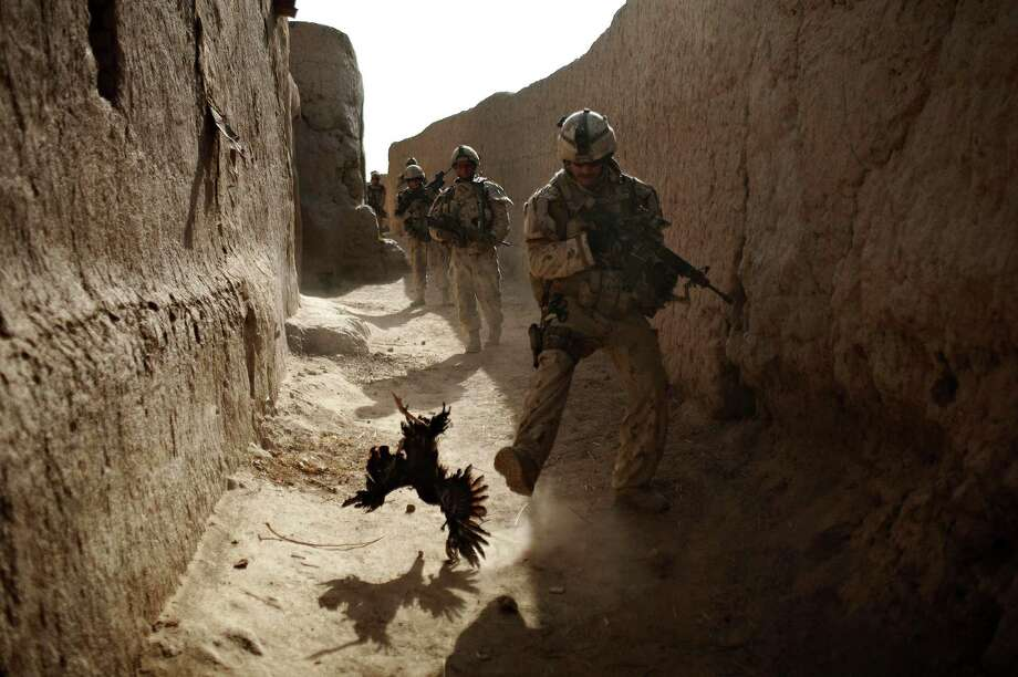 In this Saturday, Sept. 11, 2010 file photo made by Associated Press photographer Anja Niedringhaus, a Canadian soldier with the 1st RCR Battle Group, The Royal Canadian Regiment, chases a chicken seconds before he and his unit were attacked by grenades shot over the wall during a patrol in Salavat, southwest of Kandahar, Afghanistan. Niedringhaus, 48, an internationally acclaimed German photographer, was killed and an AP reporter was wounded on Friday, April 4, 2014 when an Afghan policeman opened fire while they were sitting in their car in eastern Afghanistan. Photo: Anja Niedringhaus, Associated Press / AP
