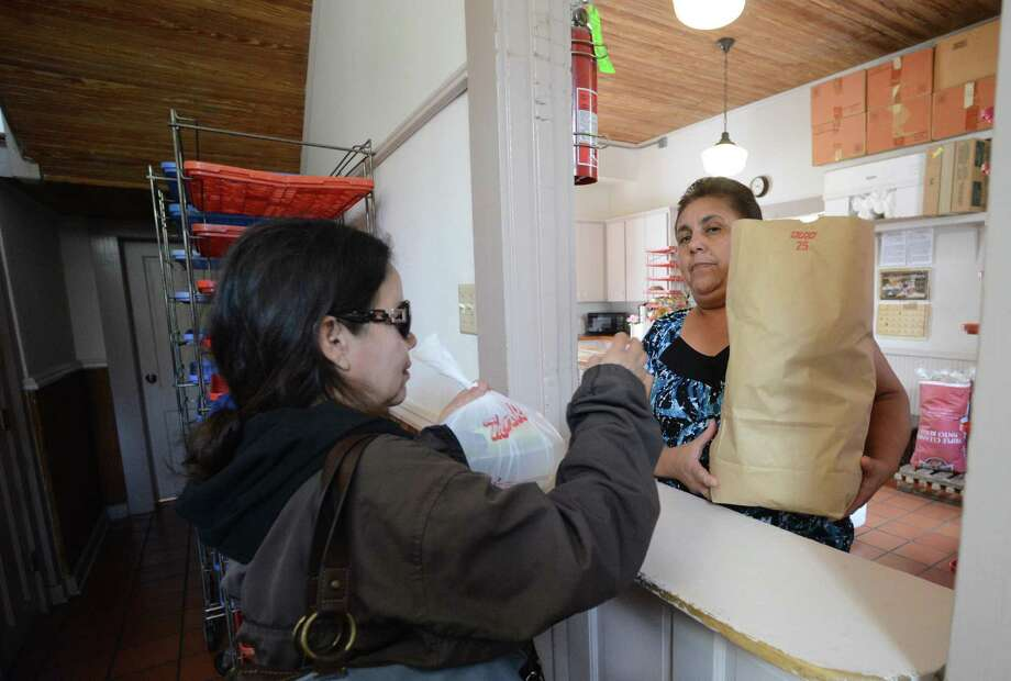 Martha Delgado (left) receives a bag of food from Maria Torres at the The Little Church at La Villita food assistance program. The program is in danger of being shut down. Photo: Billy Calzada / San Antonio Express-News / © 2014 San Antonio Express-News
