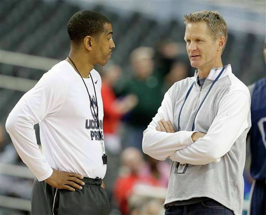 Connecticut head coach Kevin  Ollie and former professional basketball player Steve Kerr talk during  Connecticut's practice for their NCAA Final Four tournament college  basketball semifinal game Friday, April 4, 2014, in Dallas. Connecticut  plays Florida on Saturday, April 5, 2014. (AP Photo/Eric Gay)