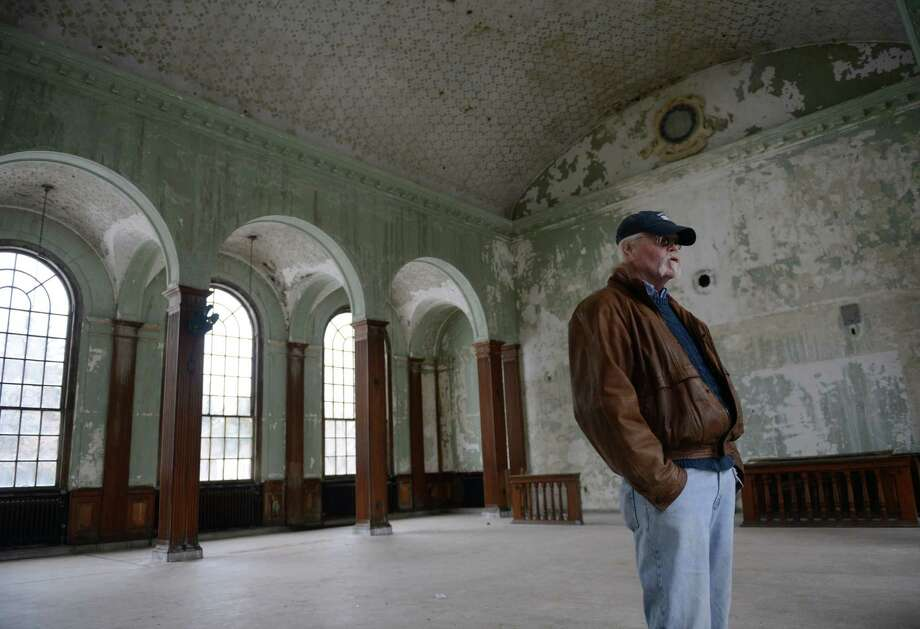 Fairfield Hills Authority member Ross Carley stands inside of Stratford Hall, formerly a library and cafeteria, on the Fairfield Hills campus in Newtown, Conn. on Wednesday, March 12, 2014.  The 185-acre plot, formerly used as a psychiatric hospital, has been undergoing development since the Town of Newtown purchased the property in 2004.  The property currently houses the Newtown Town Hall and Youth Academy, along with several ball fields and walking trails.  The Newtown emergency services center is currently undergoing construction and plans are set to construct the Newtown Parent Connection on the site also.  Other possible prospects for the site include the EverWonder Children's Museum, 12.14 Foundation, Cultural Arts Commission and a community center made possible by a grant from General Electric. Photo: Tyler Sizemore / The News-Times