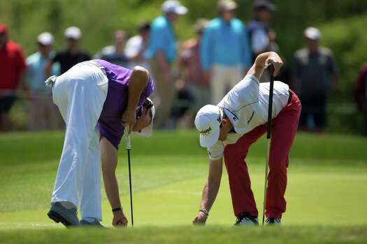 Phil Mickelson, left, and Keegan Bradley, right, place ball markers on the second hole green during the round two of the Shell Houston Open at the Golf Club of Houston, Friday, April 4, 2014, in Humble. Photo: Marie D. De Jesus, Houston Chronicle / © 2014 Houston Chronicle