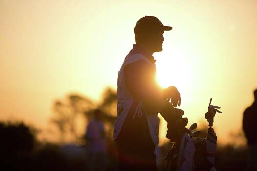 Erik Compton's caddie is silhouette against the sunrise at the  Golf Club of Houston driving range during the Shell Houston Open, Friday, April 4, 2014, in Humble. Photo: Marie D. De Jesus, Houston Chronicle / © 2014 Houston Chronicle