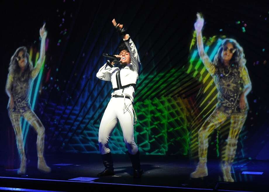 Janelle Monae, center, performs alongside holograms of M.I.A. during a launch party for the Audi M3 on Thursday, April 3, 2014 in West Hollywood, Calif. Photo: Chris Pizzello, Associated Press