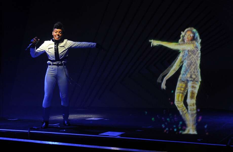 Janelle Monae, left, performs alongside a hologram of M.I.A. during a launch party for the Audi M3 on Thursday, April 3, 2014 in West Hollywood, Calif. Photo: Chris Pizzello, Associated Press