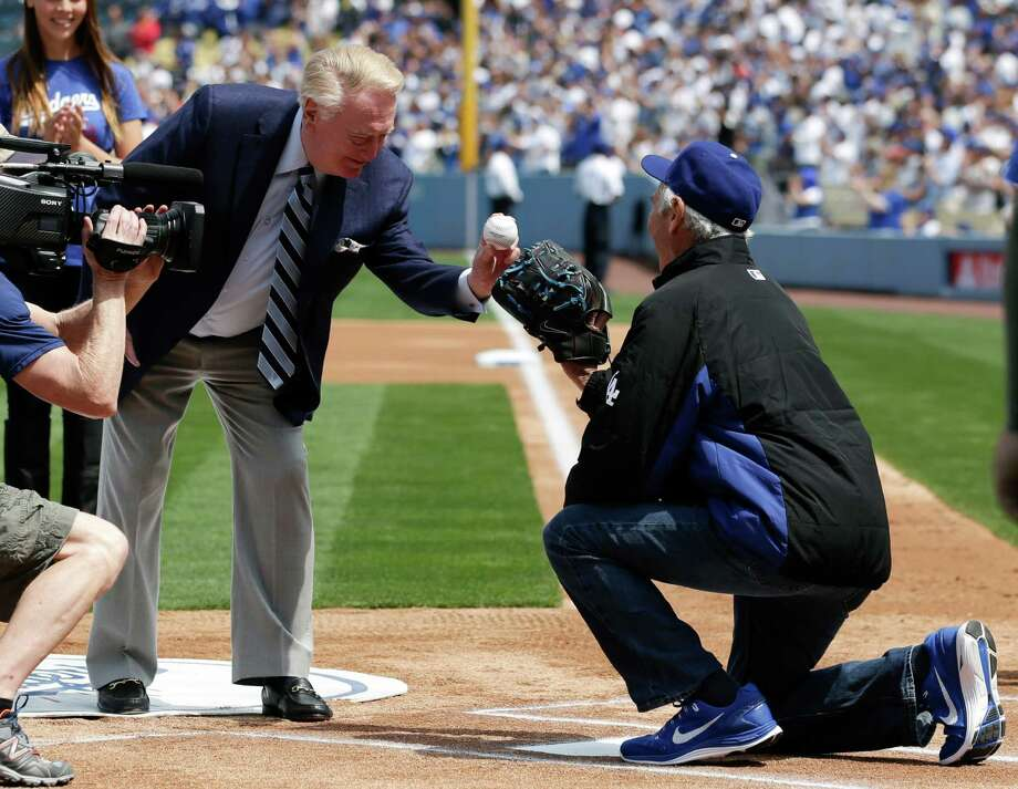 Los Angeles Dodgers broadcaster Vin Scully, left, throws the ceremonial first pitch to former Los Angeles Dodgers pitcher Sandy Koufax before a baseball game between the Los Angeles Dodgers and the San Francisco Giants on Friday, April 4, 2014, in Los Angeles. (AP Photo/Jae C. Hong) Photo: Jae C. Hong, Associated Press / AP