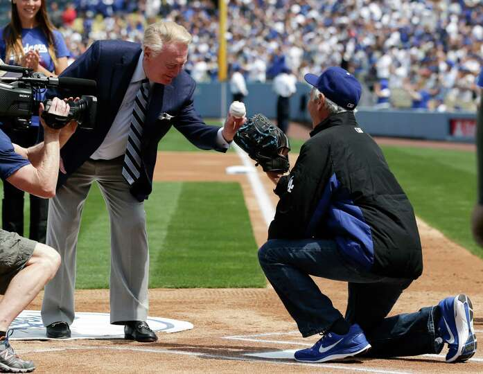 Los Angeles Dodgers broadcaster Vin Scully, left, throws the ceremonial first pitch to former Los An