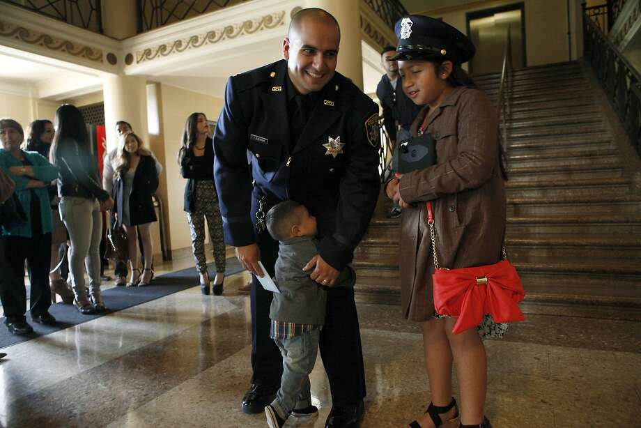 Recruit Thomas Quezada gets a hug from his son Alexis, 2, while his daughter Natalia, 9, wears his police hat. Photo: Michael Short, The Chronicle
