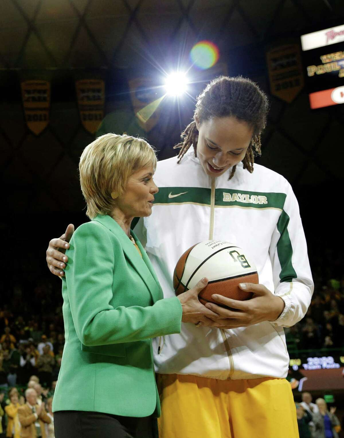 Baylor head coach Kim Mulkey left, hands Brittney Griner, right, a trophy basketball during a pregame ceremony before an NCAA college basketball game against Texas Saturday, Feb. 23, 2013, in Waco, Texas. Griner was honored before the game for becoming the eighth Division I woman with 3,000 career points in Monday's win at No. 3 Connecticut. She moved up to No. 5 on the career list, passing Cindy Blodgett (Maine), Cheryl Miller (Southern California) and Chamique Holdsclaw (Tennessee). She's six points behind UConn's Maya Moore. Baylor defeated Texas 67-47. (AP Photo/Tony Gutierrez)