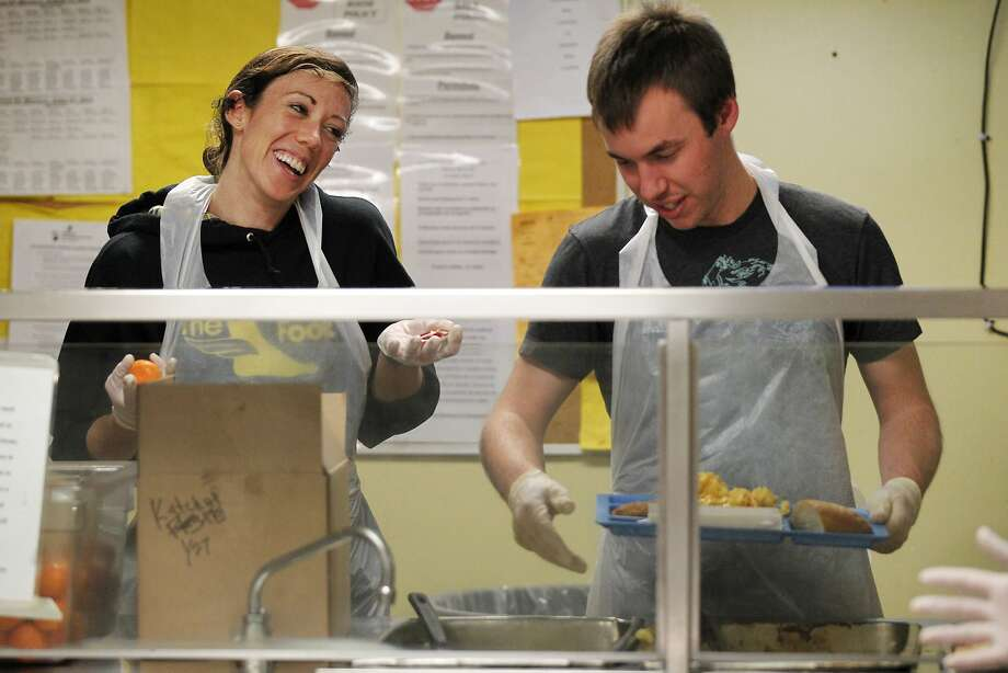 Google employee volunteers Colleen Ryan (left) and Morgan Conbere joke around as they serve clients at Episcopal Community Services, which provides a range of assistance. Photo: Leah Millis, San Francisco Chronicle