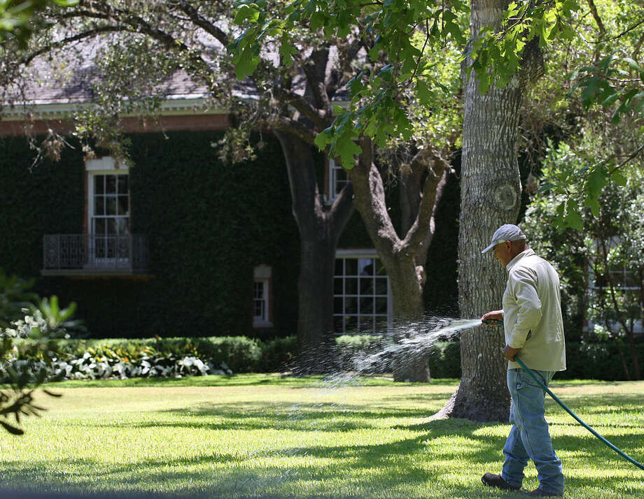 A worker waters the lawn at a San Antonio residence that is reported to be one of the top water users in the county. One of our readers implores residents to conserve by obeying restrictions. Photo: Express-News File Photo / SAN ANTONIO EXPRESS-NEWS