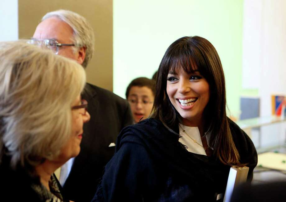 Eva Longoria waits to order at the Dairy Queen in Rivercenter mall after speaking at the Accion 20th anniversary kick off luncheon on Friday April 4, 2014. Longoria, Howard Buffett, son of billionaire Warren Buffett, spoke at the luncheon at the Marriott Rivercenter Hotel.  The Eva Longoria Foundation and the Howard G. Buffett Foundation have joined with Accion Texas to create a new small business loan fund for Latina entrepreneurs in Texas.  Since 2013 the fund has made 58 micro loans totaling more than $500,000. Photo: Helen L. Montoya, San Antonio Express-News / ©2013 San Antonio Express-News