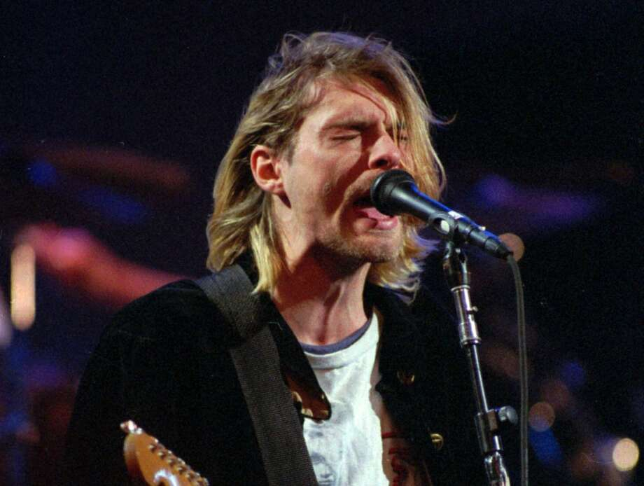 This Dec. 13, 1993 file photo shows Kurt Cobain of the Seattle band Nirvana performing in Seattle, Wash. It's been two decades since the Nirvana frontman took his own life yet he remains on in the thoughts of those he influenced and entertained. He's a touchstone for young musicians clutching guitars the world over and his story is a tale of both inspiration and caution. His influence still ripples across the surface of pop music and his shadow even looms in the hip-hop world where he's been a referenced by Jay Z, Kanye, Kendrick Lamar, Drake and Jay Electronica in various ways recently. (AP Photo/Robert Sorbo, file) Photo: ROBERT SORBO, Associated Press