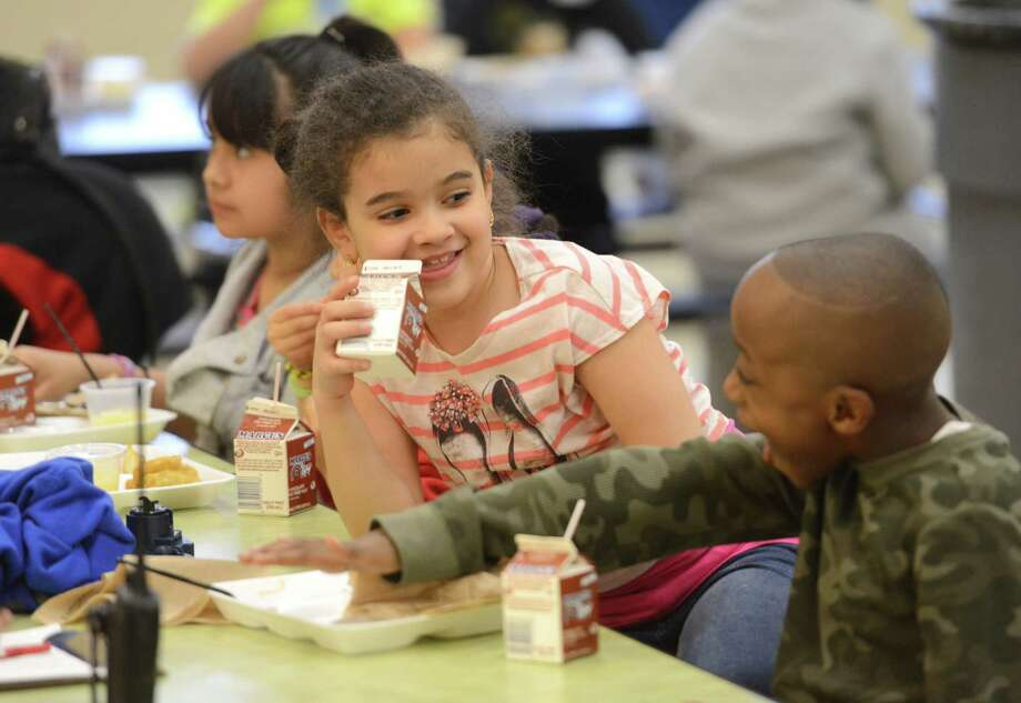 Second-graders Mikaelly Souza and Kemonte Gregory laugh while eating at the after-school supper program at Ellsworth Elementary School in Danbury, Conn. Friday, April 4, 2014.  The USDA-sponsored program, which started Tuesday, will run every Monday through Friday and provide a free dinner to any child at the school's after school program since so many of the children are eligible for free or reduced-price lunch. Photo: Tyler Sizemore / The News-Times